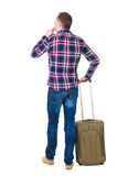 Back view of man with  green suitcase looking up. Stock Images