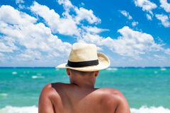 Back view of a man relaxing at tropical beach. Back view of a man with hat relaxing at tropical beach Stock Photo