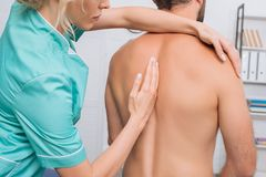 back view of man having chiropractic adjustment stock photo