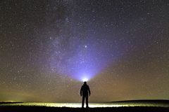 Back view of man with head flashlight standing on green grassy field under beautiful dark blue summer starry sky. Night. Photography, beauty of nature concept royalty free stock photography