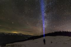 Back view of man with head flashlight standing on snowy valley under beautiful dark blue winter starry sky, bright blue beam on royalty free stock photos