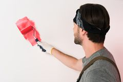 Back view of man in headband painting wall in red by paint. Roller royalty free stock image