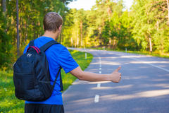 Back view of man hitchhiking on forest road. Back view of young man hitchhiking on forest road Stock Photography