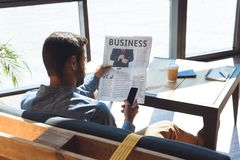 back view of man holding newspaper and using smartphone while sitting Royalty Free Stock Photos