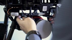 Back view of a man installing camera in quadrocopter, preparation for the flight. Clip. Close up for the process of. Back view of a man installing camera in stock video footage