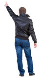 Back view of man in jacket  pointing. Stock Photo