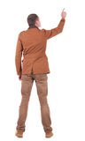 Back view of  man in jacket  pointing. Royalty Free Stock Image