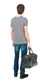 Back view of man in jeans with bag in his hand. Stock Photos