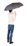 Back view of man in jeans under an umbrella. Royalty Free Stock Photos