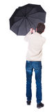 Back view of man in jeans under an umbrella. Standing young guy. Stock Image