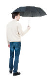 Back view of man in jeans under an umbrella. Stock Photography