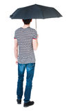 Back view of man in jeans under an umbrella. Royalty Free Stock Photo