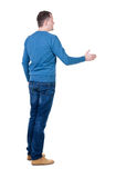 Back view of man in movement reaches out to shake hands. Stock Images