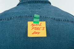 Back view of man with note on sticky tape with april fools day lettering on back, april fools day holiday concept royalty free stock photos