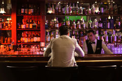 Back view of a man ordering drink to a bartender. While sitting at the counter at the pub Royalty Free Stock Images