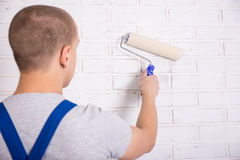 Back view of man painter in workwear painting brick wall with pa Royalty Free Stock Photo