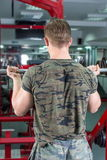 Back view of a man performing biceps workout. Back view of a man performing barbell curl at the gym. Biceps workout Stock Photo
