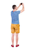 Back view of man photographing.  tourist in shorts. Royalty Free Stock Images
