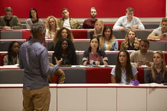 Back view of man presenting to students at a lecture theatre Stock Images