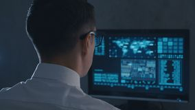 Back view of man programmer in glasses and white shirt working at computer in the data center. Back view of man programmer in white shirt and glasses working at stock footage