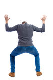 Back view. man  protects hands from what is falling  above. Royalty Free Stock Photos