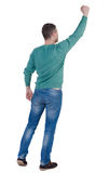 Back view of  man. Raised his fist up in victory sign.   Rear vi. Back view of  man.  Raised his fist up in victory sign.  Happy guy in blue pullover and jeans Royalty Free Stock Image