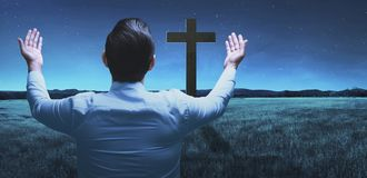 Back view of man raising hand while praying to god. Over night background stock photography