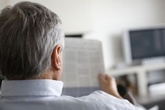 Back view of man reading newspaper Stock Photo