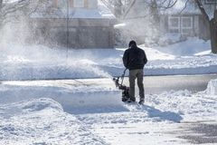 Man Removing Snow with a Snowblower on a Sunny Day  2. Back View of a Man Removing Snow with a Snowblower on a Sunny Day  2 Royalty Free Stock Image