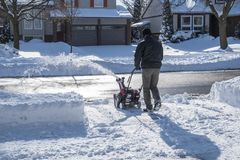 Man Removing Snow with a Snowblower on a Sunny Day  1. Back View of a Man Removing Snow with a Snowblower on a Sunny Day  1 Stock Photos