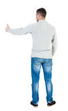 Back view of  man in shirt shows thumbs up. Stock Photo