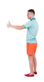 Back view of  man in shorts shows thumbs up. Royalty Free Stock Photography