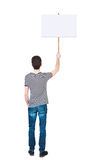 Back view man showing sign board. man holds information plate. Royalty Free Stock Photography