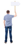 Back view  of man showing a sign board. Stock Photos