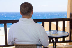 Back view of man sitting on balcony with sea view. Back view of man sitting on balcony with beautiful sea view Royalty Free Stock Photos