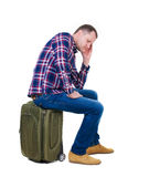 Back view of a man sitting on a suitcase. stock photos