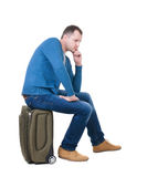 Back view of a man sitting on a suitcase. royalty free stock photos