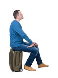 Back view of a man sitting on a suitcase. Royalty Free Stock Photography