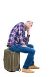 Back view of a man sitting on a suitcase. Royalty Free Stock Images