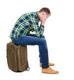 Back view of a man sitting on a suitcase. Royalty Free Stock Photo