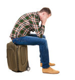 Back view of a man sitting on a suitcase. Stock Photo