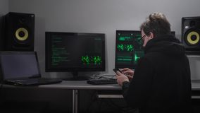 Back view of a man sitting at the table using his smartphone. Cyber spy hacking computer system with the help of his stock footage