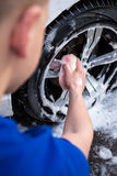 Back view of man with sponge washing car wheel Royalty Free Stock Images