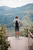 Back view of the man standing at view point on the high. And watching mountain landscape Stock Photo