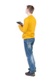 Back view of man with tablet. Standing young guy. Royalty Free Stock Photos