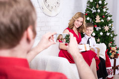 Back view of man taking photo of his wife and son with Christmas. Back view of young men taking photo of his wife and son with Christmas tree Royalty Free Stock Image