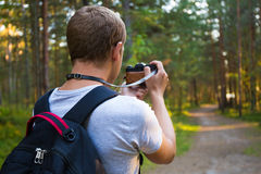 Back view of man taking a photo with retro camera Royalty Free Stock Photo