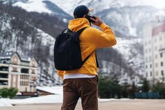 Back view. Man tourist in yellow hoodie with black backpack stands on background of high snowy mountains, talking on mobile phone royalty free stock photography