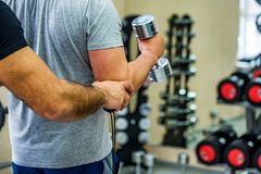 Back view man trains biceps with trainer in gym. Back view of a man holding dumbbell and trainig biceps in modern gym Stock Photos