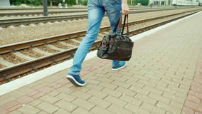 Back view: A man with a travel bag goes along the railroad. Only legs are visible in the frame. Steadicam shot. Back view: A man with a travel bag goes along the stock video